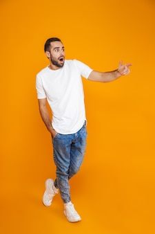 Foto de cuerpo entero de hombre sorprendido de 30 años en camiseta y jeans apuntando con el dedo a un lado mientras está de pie, aislado