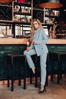 Foto de cuerpo entero de la joven y bella mujer rubia en elegante traje posando en el interior de la cafetería. concepto de moda
