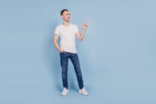Foto de cuerpo entero del joven feliz mirada positiva smiel indica dedo espacio vacío anuncio seleccionar sugerir aislado sobre fondo de color azul