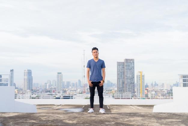 Foto de cuerpo entero de joven guapo multiétnico contra la vista de la ciudad