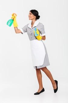 Foto de cuerpo entero de la joven morena mais en guantes protectores uniformes y amarillos rociando el limpiador en la ventana