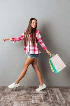 Foto de cuerpo entero de joven mujer bonita, caminando de compras, sosteniendo bolsas de compras