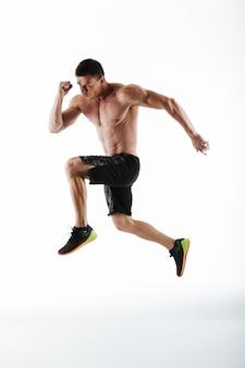 Foto de cuerpo entero del joven y poderoso hombre deportivo saltando