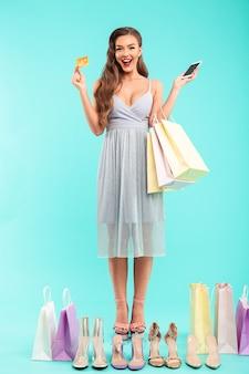 Foto de cuerpo entero de una mujer adicta a las compras sonriente sosteniendo bolsas de la compra y comprando zapatos de verano con un teléfono inteligente y una tarjeta de crédito, aislado sobre una pared azul