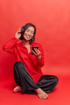 Foto de cuerpo entero de una mujer asiática morena que tiene una mente tranquila en auriculares inalámbricos, escucha música relajante de una lista de reproducción, tiene un celular en la mano, descarga canciones disfruta del tiempo en casa aislado sobre una pared roja