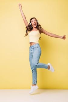 Foto de cuerpo entero de una mujer bonita positiva de 20 años con cabello largo y castaño en ropa casual cantando y regocijándose mientras escucha música a través de auriculares, aislado sobre una pared amarilla