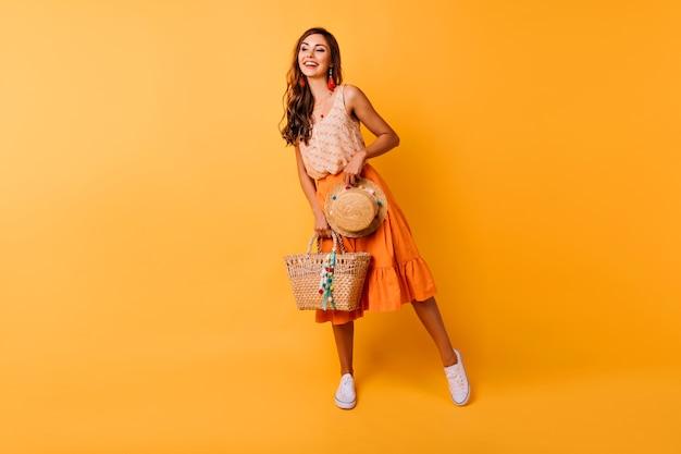 Foto de cuerpo entero de mujer inspirada con accesorios de verano. modelo femenino de jengibre feliz en falda naranja con sombrero y bolso.