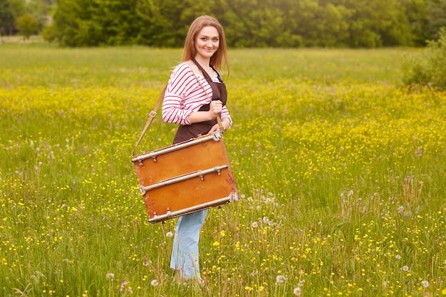 Foto de cuerpo entero de una mujer rubia que usa ropa casual, termina de pintar, lista para irse a casa, posando con una agradable expresión facial