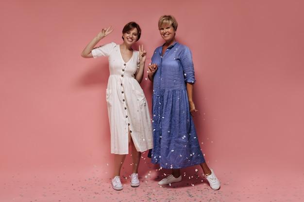 Foto de cuerpo entero de niña con pelo corto en vestido blanco y zapatillas de deporte sonriendo, mostrando el signo de la paz y posando con una mujer rubia sobre fondo rosa