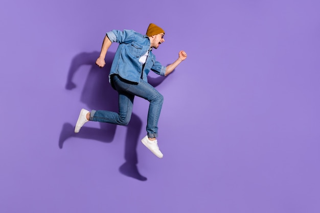 Foto de cuerpo entero de tamaño corporal de hombre corriendo rápido y gritando en aspiración de productos con descuento saltando aislado sobre fondo de color púrpura vivo