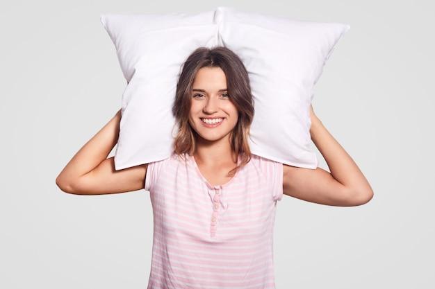 Foto de una dama alegre con una gran sonrisa, sostiene una almohada detrás de la cabeza, usa una camiseta informal, disfruta de un buen descanso y sueños agradables
