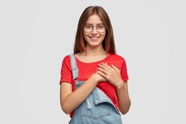 La foto de una dama amigable y complacida mantiene las manos en el pecho o el corazón, siendo movida por palabras positivas