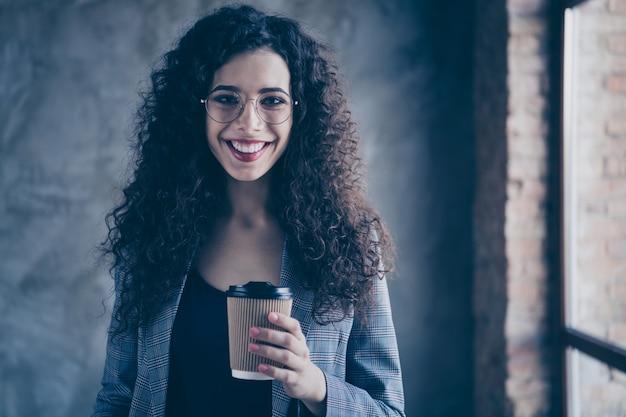 Foto de dama de negocios beber espresso en la moderna sala de estilo industrial de ladrillo