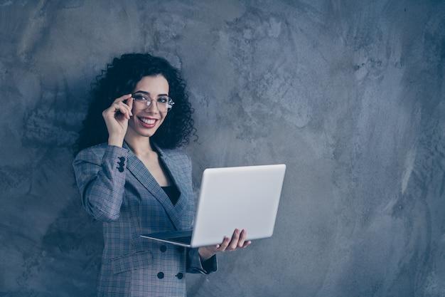 Foto de dama de negocios inteligente sosteniendo portátil tocando especificaciones aisladas sobre muro de hormigón