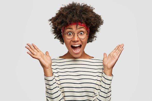 Foto de una dama negra sorprendida sorprendida y llena de alegría junta las manos, exclama con expresión de sorpresa