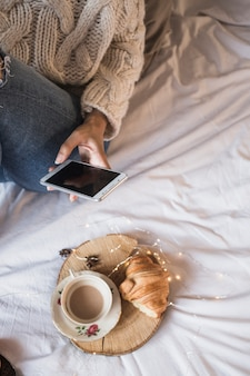 Foto de mujer tomando café y croissant