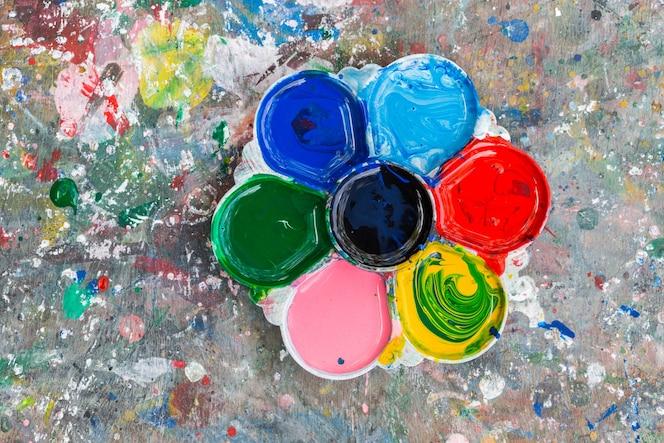 Foto de una paleta de artistas cargada de varias pinturas de color en el fondo de la tabla de madera