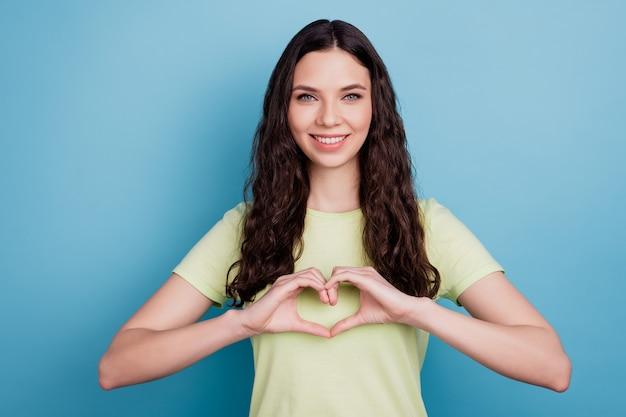 Foto de los dedos románticos de la niña inspirada en ensueño muestran el gesto del corazón sobre fondo azul