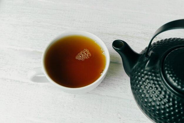 Foto de deliciosa taza de té negro sobre la mesa de madera blanca