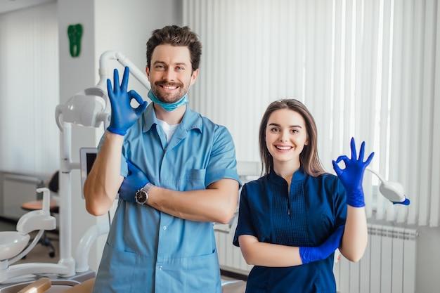 Foto de dentista sonriente de pie con los brazos cruzados con su colega, mostrando el signo de bien.