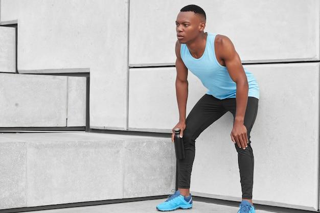 Foto de deportista cansado parado cerca de una pared blanca, mantiene las manos en las rodillas, siente fatiga, sostiene una botella negra con agua, posa cerca de los escalones, corre para entrenar la resistencia. cansancio, concepto deportivo