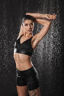 Foto de deportista joven y saludable posando mientras está parado bajo las gotas de lluvia después de trotar, aislado sobre fondo negro