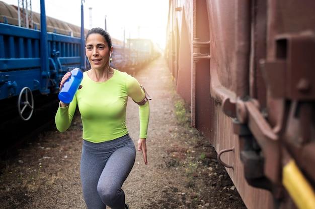 Foto de deportista sosteniendo una botella y corriendo entre trenes en la estación de tren.