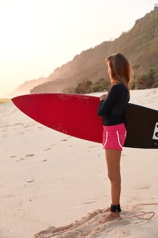 La foto de la deportista tiene buena forma corporal, usa pantalones cortos rosas y lleva una tabla de surf larga