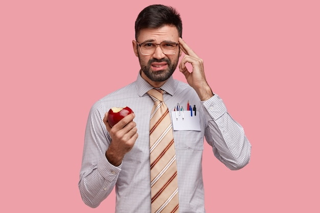 Foto de descontento joven caucásico mantiene el dedo en la sien, vestido formalmente, come manzana, recuerda algo en mente
