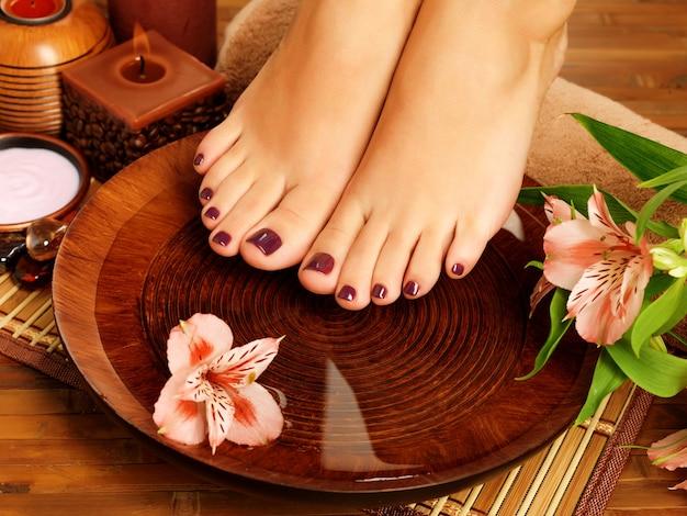Foto de detalle de pies femeninos en el salón de spa en procedimiento de pedicura. concepto de cuidado de piernas