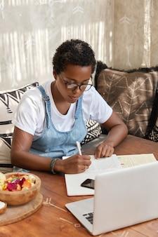 Foto de diseñador gráfico negro profesional que trabaja de forma remota, se sienta frente a la computadora portátil abierta