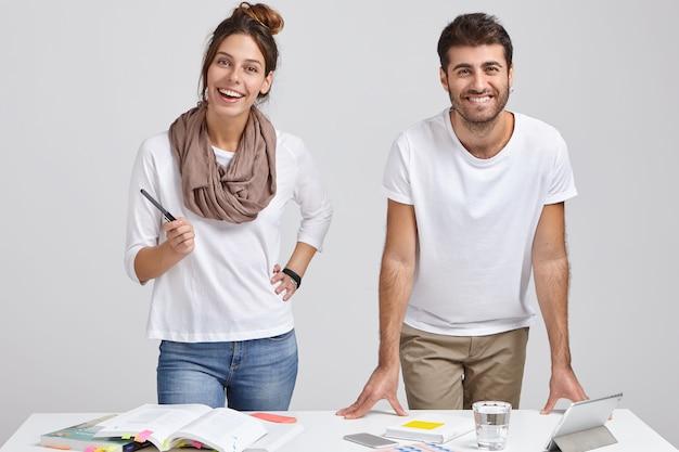 Foto de diseñadores alegres de mujeres y hombres vestidos con ropa de moda, parados cerca del escritorio blanco, estudiar literatura, hacer que el proyecto funcione en una tableta, conectado a internet inalámbrico