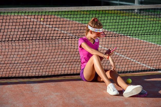 Foto de dolly de linda chica deportiva sentada en una cancha de tenis cerca de la red y utiliza un teléfono inteligente para chatear y navegar en las redes sociales en el fondo del atardecer.