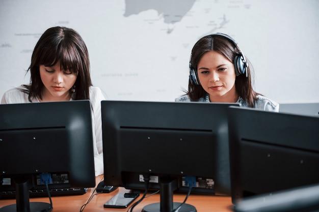 Foto de dos empleados. jóvenes que trabajan en el centro de llamadas. se acercan nuevas ofertas