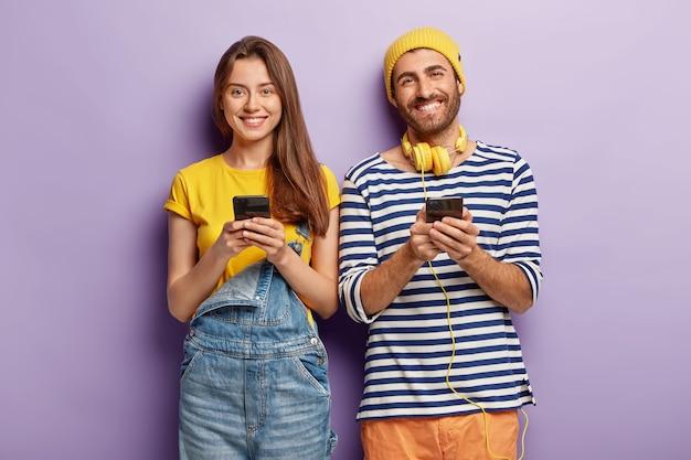 Foto de dos geeks de teléfonos inteligentes que utilizan tecnologías modernas para publicar nuevas fotos en las redes sociales