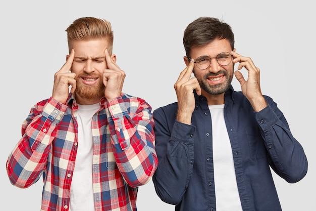 Foto de dos hombres estresados que tienen dolor de cabeza, mantienen los dedos índice en las sienes, tienen expresión facial disgustada