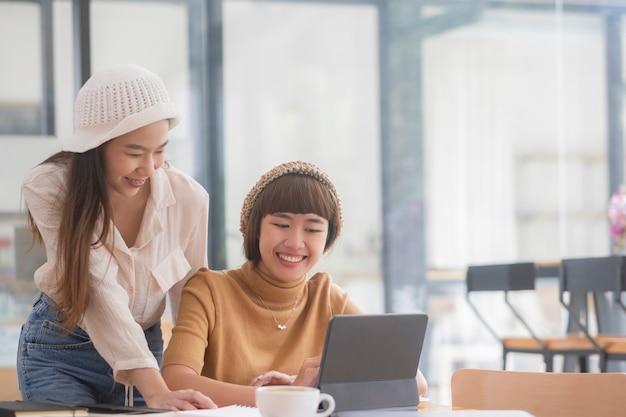 Foto de dos mujeres jóvenes trabajando juntos en tableta digital. ejecutivas creativas reunidas en una oficina con tablet pc y sonriendo.