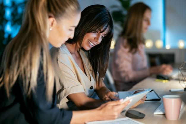 Foto de dos mujeres de negocios inteligentes que trabajan junto con una tableta digital mientras hablan en la oficina.