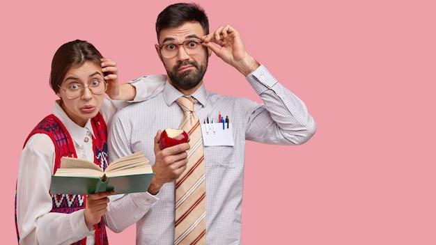 Foto de dos nerds masculinos y femeninos sorprendidos que miran con estupor, expresión de disgusto, leen el libro en voz alta, intentan aprender nueva información