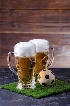 Foto de dos vasos de cerveza, balón de fútbol sobre césped verde