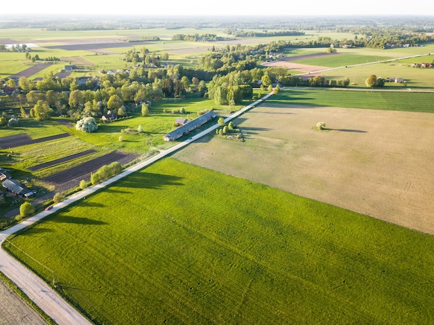 Foto de un dron de una pradera de pasto verde junto a un campo agrícola con un camino de tierra y una aldea de campo