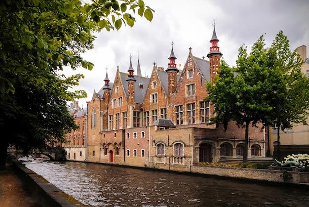 Foto de edificios históricos medievales a lo largo de un canal en brujas, bélgica