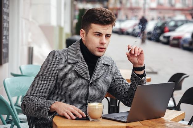 Foto de elegante hombre de negocios con mirada melancólica sentado en la cafetería afuera, fumando cigarrillos y bebiendo capuchino