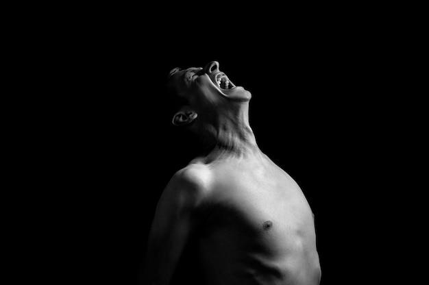 Foto emocional, hombre gritando sobre fondo negro