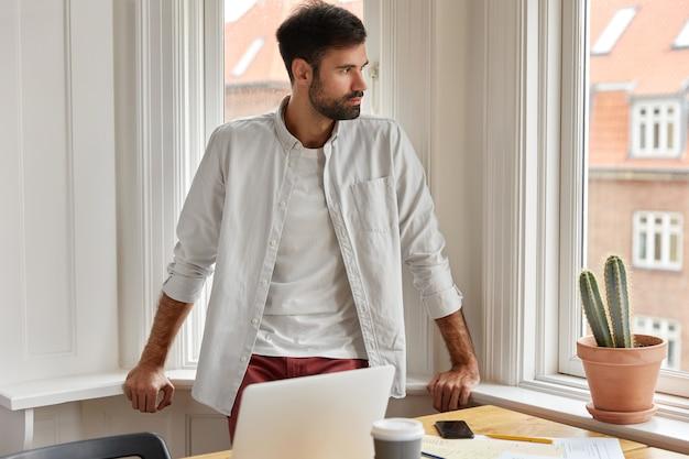 Foto de empleador masculino trabaja desde casa, se encuentra cerca de una ventana grande y escritorio con computadora portátil
