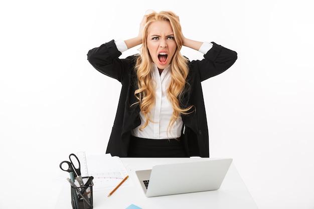 Foto de empresaria indignada sentada a la mesa y trabajando en la computadora portátil, aislado