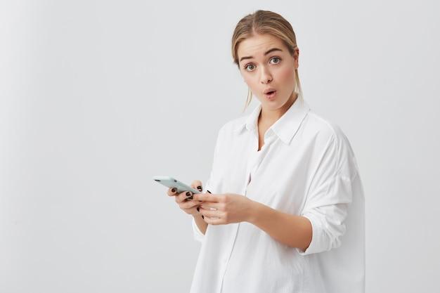 Foto de empresaria sorprendida con cabello rubio vestido con una camisa blanca sosteniendo su moderno teléfono inteligente recibiendo un mensaje sorprendido al olvidarse de una reunión importante con socios comerciales