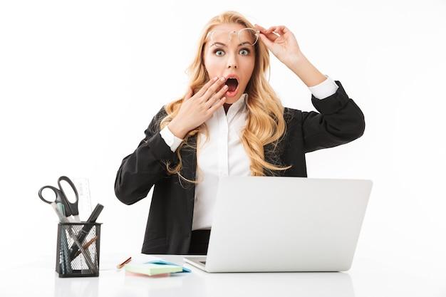 Foto de empresaria sorprendida sentada en el lugar de trabajo y trabajando en la computadora portátil, aislado