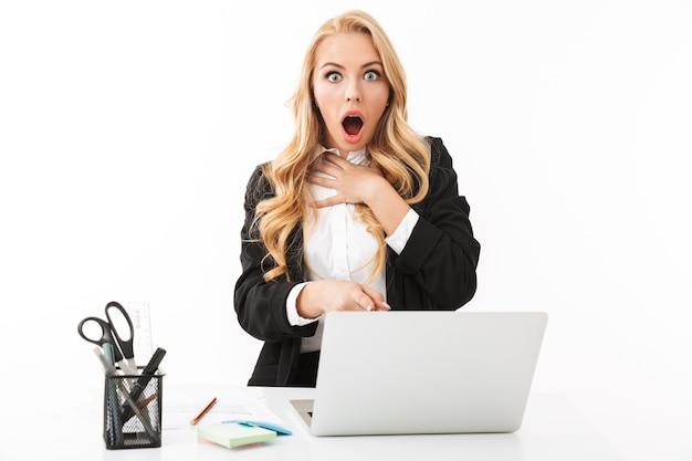 Foto de empresaria sorprendida trabajando en la oficina y usando laptop, aislado