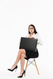 Foto de empresaria trabajadora complacida vestida con ropa formal sosteniendo un maletín lleno de billetes de un dólar mientras está sentado en una silla aislada sobre una pared blanca